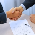 46618811 - close-up image of a firm handshake between two colleagues after signing a contract