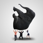 20990547 - business team is lifting heavy elephant on white background